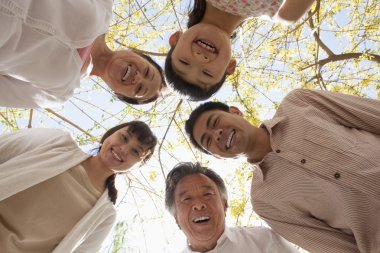 Family in a circle looking down in a park