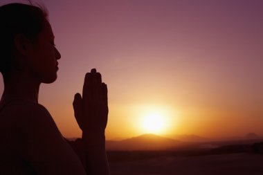 Woman with hands together in prayer pose