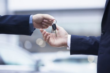 Car salesman handing over the keys for a new car