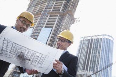Architects looking at blueprint on construction site