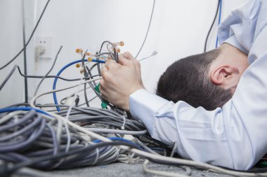 Frustrated man sort computer cables