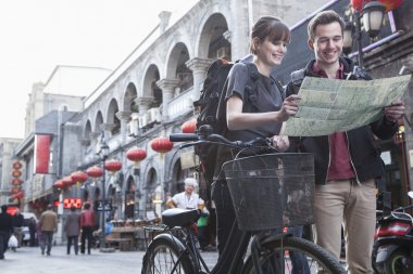 Man and woman with bicycle and map
