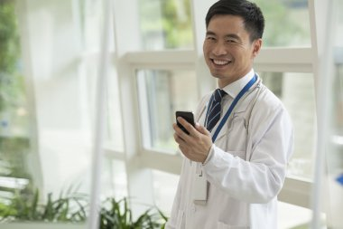 Doctor using his phone in the hospital lobby