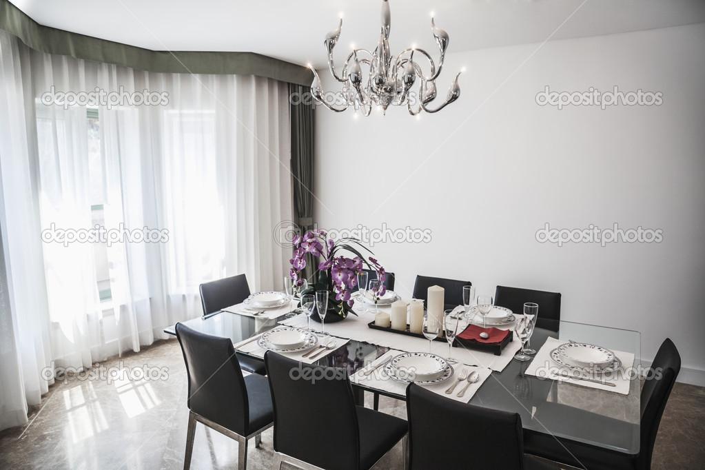 Eetkamer met modern meubilair en kroonluchter u stockfoto