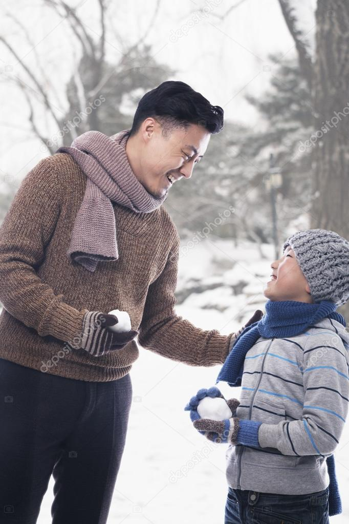 Father and son holding snowballs