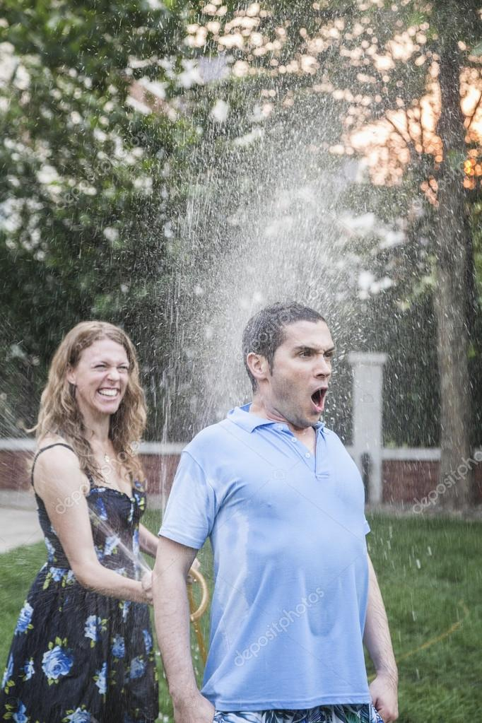 Couple playing with a garden hose