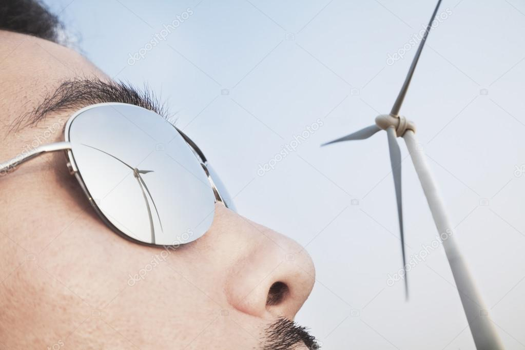 Mans face with the reflection of the wind turbine