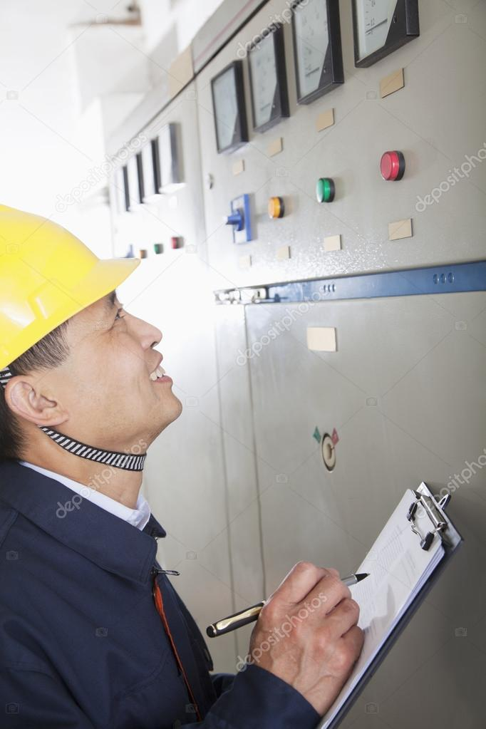 Worker checking controls in a gas plant