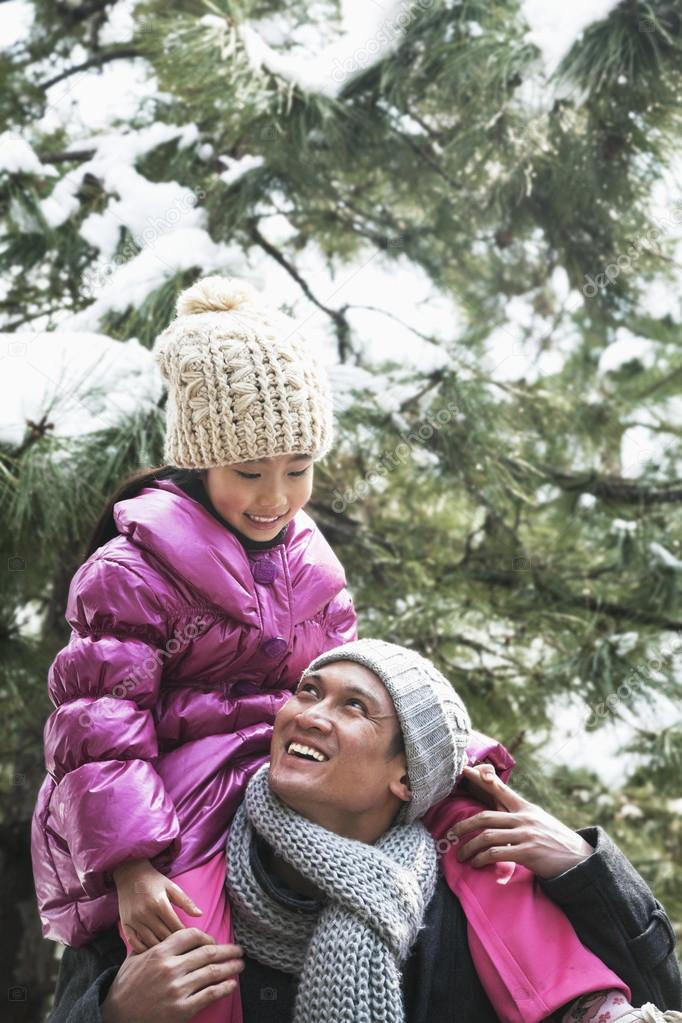 Father and daughter under tree covered in snow