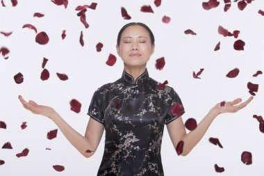 Woman with rose petals coming down around her