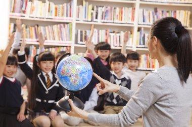 Teacher teaching geography to schoolchildren with a globe