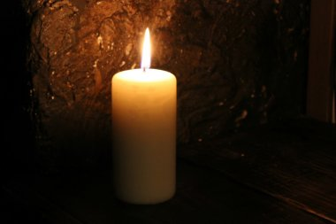 Lighted candle on a black background