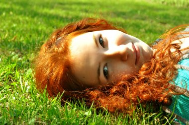 A pretty and happy redhead woman lying on green grass and smiling