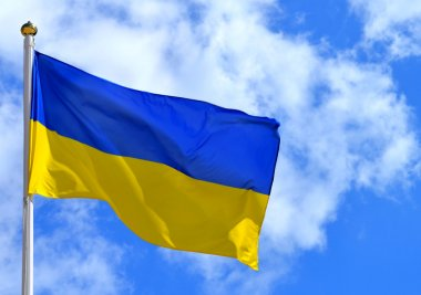 The national yellow and blue flag of Ukraine over the sky and clouds