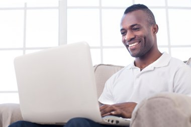 African man using computer and smiling