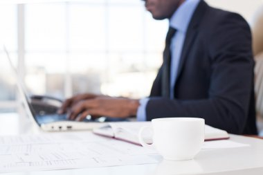 African businessman using computer with a coffee cup