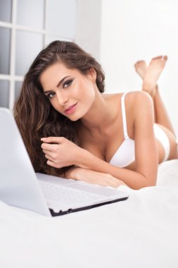 Woman in lingerie lying in bed and using computer