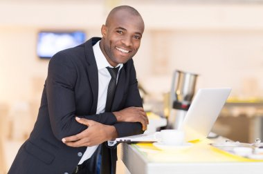 Man in formalwear using his laptop while leaning at bar