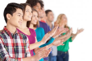 Young multi-ethnic people standing in a row and applauding