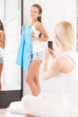 Beautiful young woman standing near the mirror with blue dress