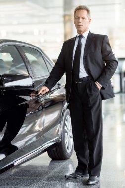 Businessman standing near car