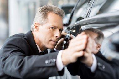Businessman examining car