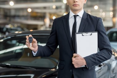 Young car salesman standing at the dealership and holding a key