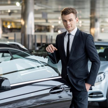 Man in formalwear leaning at the car door