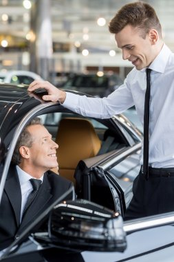 Man sitting at the front seat of the car and talking to the car salesman