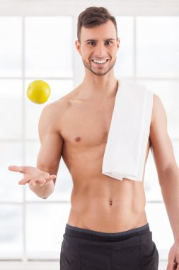 Muscular man with towel throwing up an apple