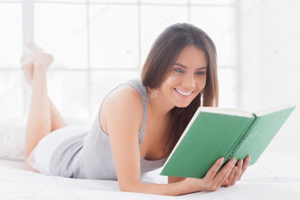 femme souriante couch dans son lit et lire un livre photographie gstockstudio 40141643. Black Bedroom Furniture Sets. Home Design Ideas