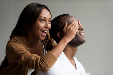African woman covering her boyfriend eyes