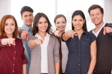 Group of people standing close to each other and pointing you