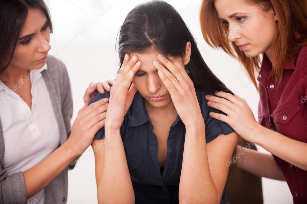 Deprimida mujer sentada en la silla mientras otras dos mujeres consolando — Foto de Stock