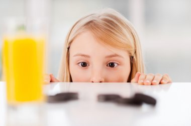 Little girl looking out from the table with cookies
