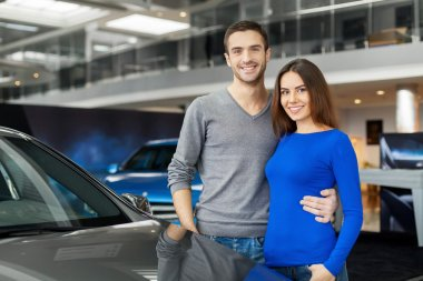 Couple standing near the car at the dealership
