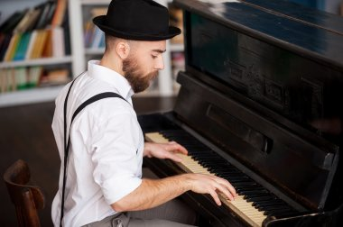 Profile of a bearded men playing piano