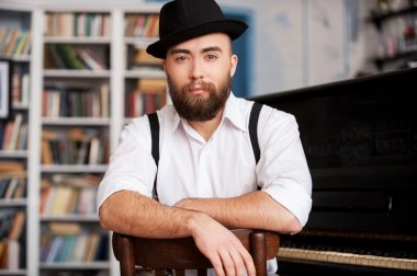 Bearded men sitting in front of his piano