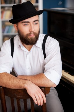 Portrait of bearded men sitting in front of his piano