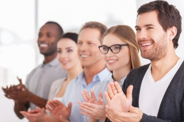 Group of cheerful business people applauding to someone