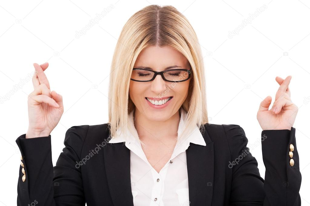 Businesswoman keeping eyes closed and fingers crossed