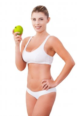 Woman in underwear holding a green apple