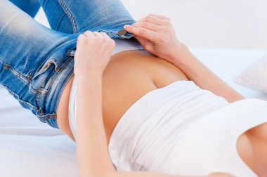 Woman pulling on tight jeans