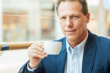 Mature man with fresh coffee.