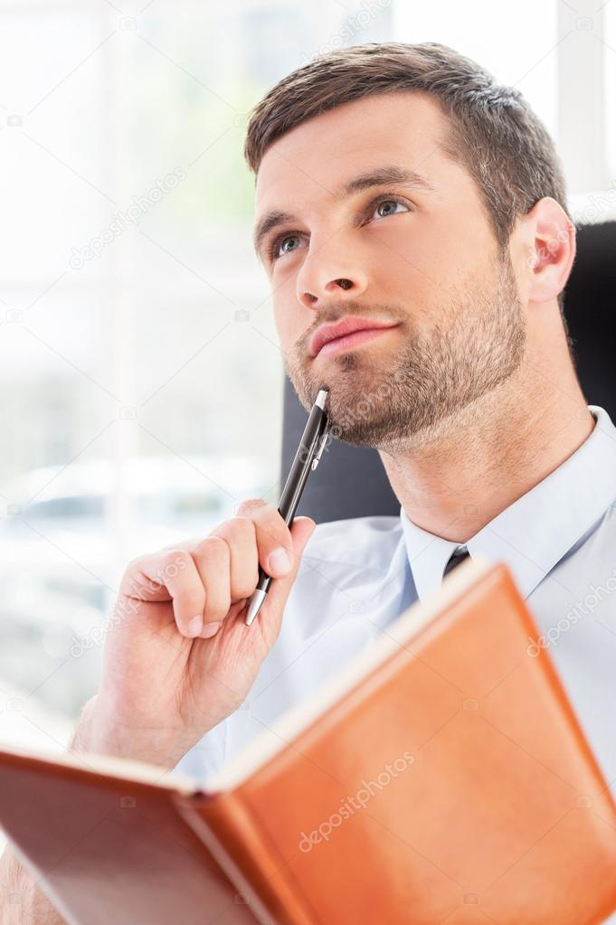 Man in shirt and tie holding note pad