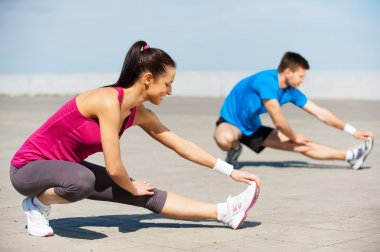 Woman and man doing stretching exercises