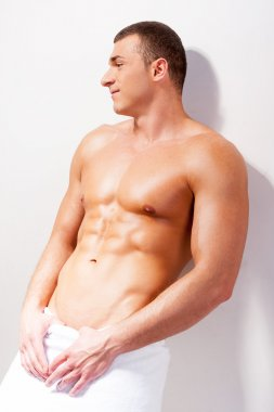 Young shirtless man covered with towel