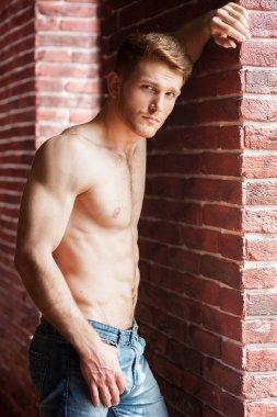 Shirtless man leaning at brick wall