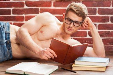 Shirtless man reading book