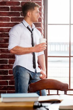 Man in shirt and tie holding coffee cup